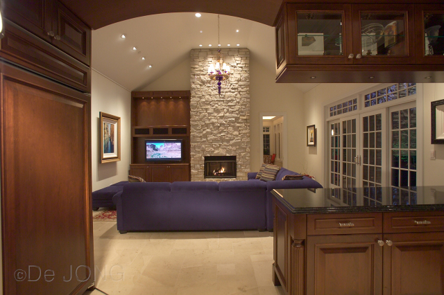 custom stone fireplace, custom wood cabinets, stone flooring.